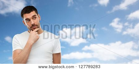 doubt, expression and people concept - man thinking over blue sky and clouds background