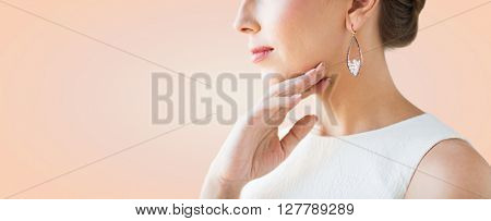glamour, beauty, jewelry and luxury concept - close up of beautiful woman face with pearl earring over beige background