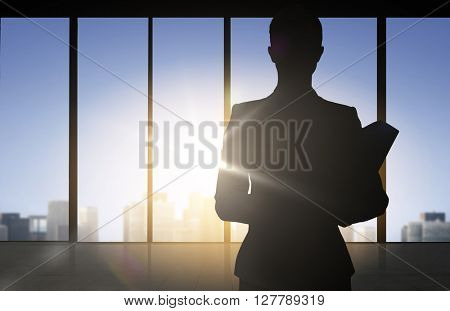 business and people concept - silhouette of woman with folders over office window background