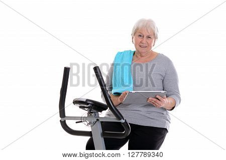 Female Senior Train With Fitness Machine And Using Tablet Pc