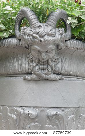 the big flowerpot is decorated with the head of the demon