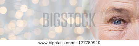 age, vision and old people concept - close up of senior woman face and eye over holidays lights background