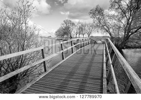 Monochrome image of a wooden foot bridge over a narrow river on a sunny but cloudy day in the spring season.
