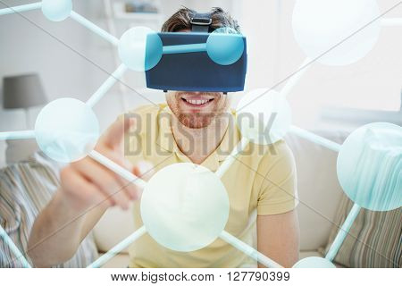 technology, gaming, entertainment and people concept - happy young man in virtual reality headset or 3d glasses playing video game with molecule projection