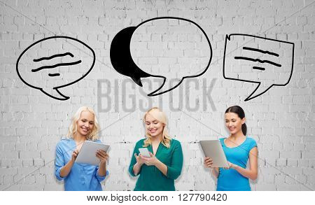 people, technology, communication and leisure concept - happy women with smartphone and tablet pc computers over gray brick wall background with text bubbles