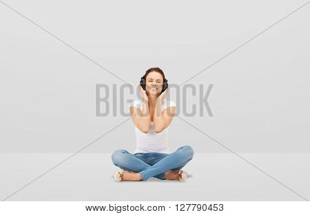 technology, music and happiness concept - smiling young woman or teen girl in headphones over gray background