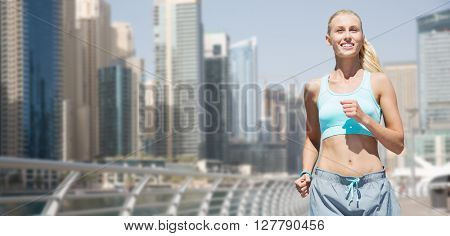 fitness, sport, friendship and healthy lifestyle concept - smiling young woman running or jogging over dubai city street background