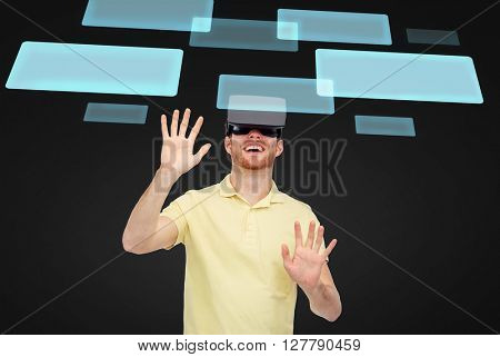 3d technology, virtual reality, entertainment and people concept - happy young man with virtual reality headset or 3d glasses playing game over black background with virtual screens