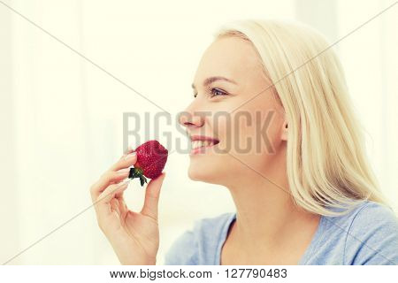 healthy eating, food, fruits, diet and people concept - happy woman eating strawberry at home