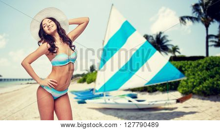 people, summer vacation, tourism and travel concept - happy young woman in bikini swimsuit and sun hat over sailing boats on tropical beach background