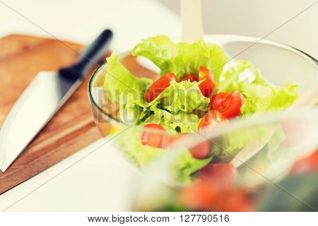 diet, vegetable food, healthy eating and objects concept - close up of vegetable salad with cherry tomato and lettuce in glass bowl