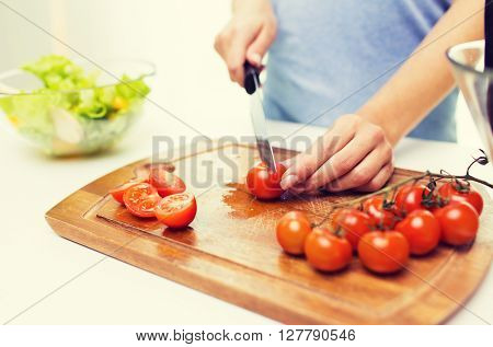 healthy eating, cooking, vegetarian food, dieting and people concept - close up of woman chopping tomatoes with knife on cutting board