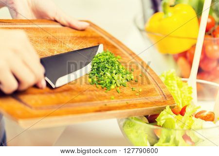 healthy eating, cooking, vegetarian food, diet and people concept - close up of woman adding chopped green onion to salad