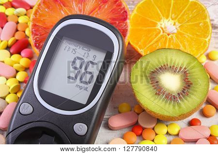 Glucometer with result of measurement sugar level fresh natural fruits and medical pills tablets and supplements diabetes healthy lifestyle and nutrition
