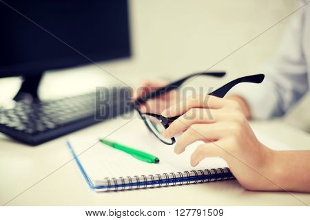 business, people, technology, vision and education concept - close up of woman hands holding eyeglasses with computer and notebook at table in office