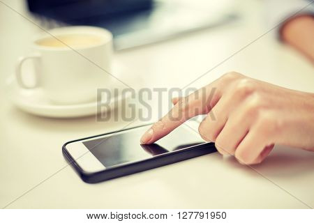 business, technology, communication, leisure and people concept - close up of woman hand with smartphone and coffee