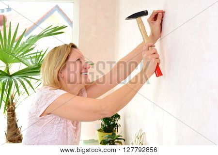 Woman Redecorate Home And Working With Hammer