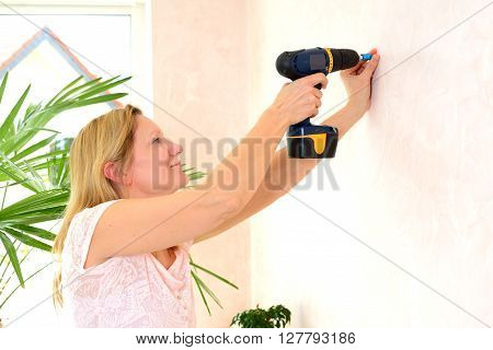 blond woman redecorate home and working with cordless screwdriver