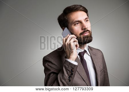 Closeup of man in suit talking on the phone on grey background