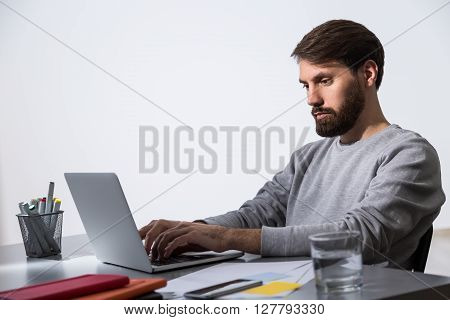 Bearded businessman working on laptop at office desk with glass of water and office tools. Sideview