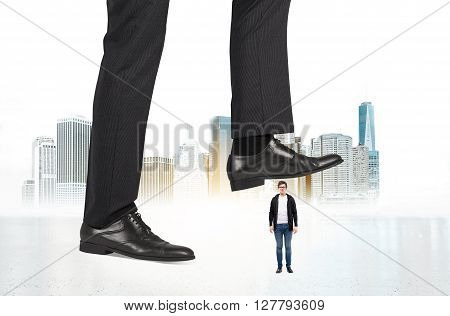 Abuse of authority concept with huge businessman foot stepping on a male miniature on New York city background