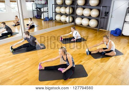 Workout team doing stretching excerises for flexibility and balance at the fitness gym.