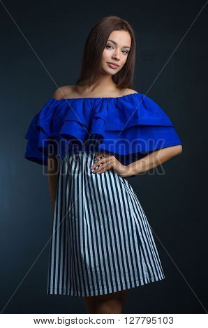 Beautiful Girl In The Dress Topic: Charming Brunette In A Blue Dress In The Studio On A Dark Backgro