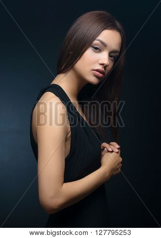 Beautiful Girl In The Dress Topic: Charming Brunette In A Black Dress In The Studio On A Dark Backgr