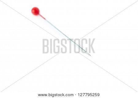 Small sewing push pin needle with red head isolated over the white background ** Note: Shallow depth of field