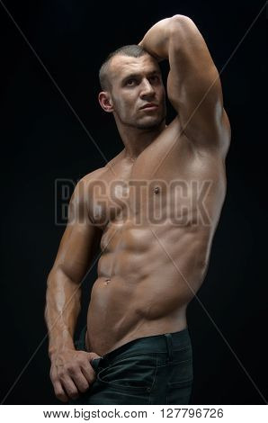 Bodybuilder And Strip Theme: Beautiful With Pumped Muscles Naked Man Posing In The Studio On A Dark