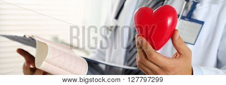 Male Medicine Doctor Hands Hold Red Toy Heart And Cardiogram Chart