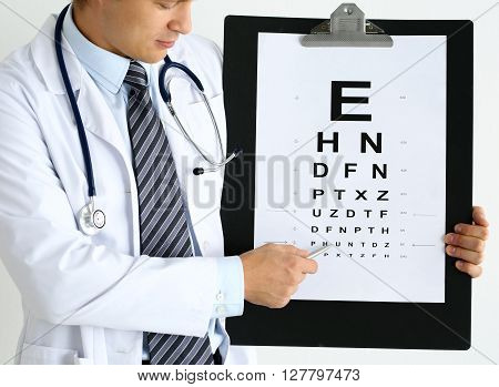 Medicine doctor hold big clipboard pad with eyesight check table and point with silver ballpoint pen to it. Excellent vision laser surgery alternative driver certificate examination concept