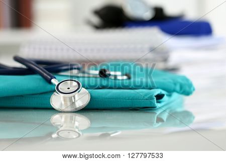 Medical Stethoscope Head Lying On Green Doctor Uniform