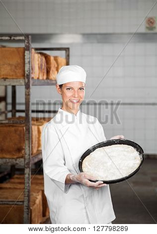Female Baker Showing Dough Tray While Standing At Bakery