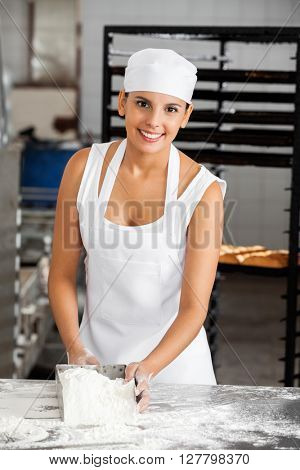 Smiling Female Baker Holding Flour Scoop At Table