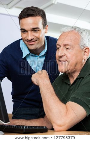 Smiling Teacher Using Computer With Senior Student