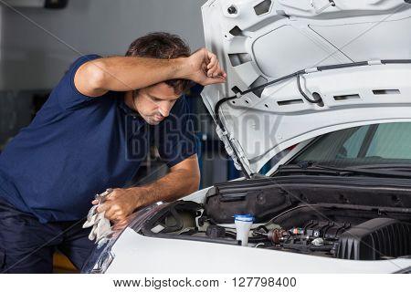 Male Mechanic Examining Car Engine