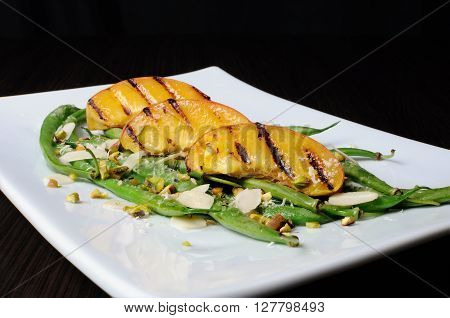 Salad of green beans peaches almonds pistachios and sprinkled with Parmesan