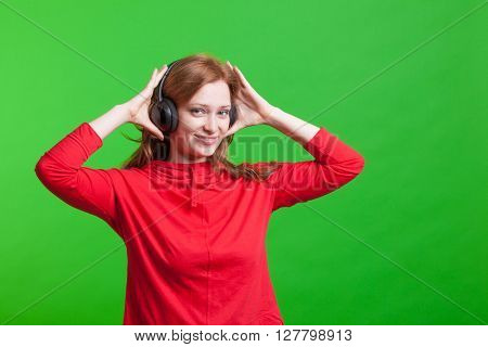 Woman listening music on headphones, green background