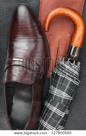 Male set of fashion accessories shoes umbrella gloves lying on the natural skin