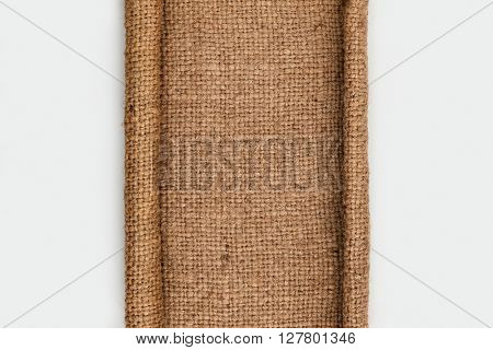 Frame of burlap with curled edges in the form of a scroll lies on a white background top view