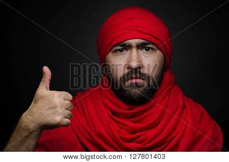 Turkish and Arabic theme: beautiful Arabic man with a beard in a red scarf showing gestures isolated on black background in studio shot