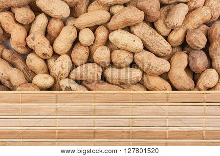 Peanuts in their shell and bamboo mat with place for your text