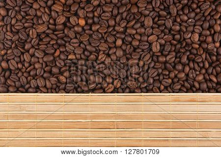 Roasted coffee beans and a bamboo mat with place for your text