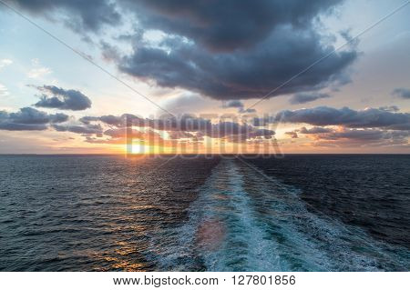 A beautiful orange sunset at sea in wake of ship