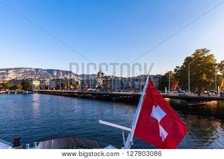 Geneva Switzerland - September 9 2015 - Tourists taking the cruise ship on the lake Geneva at dusk with view of Geneva cityscape at sunset Switzerland