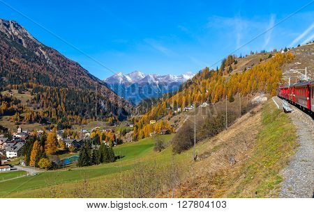 Travel with train of Rhaetian Railway in golden autumn through the line of Glacier Express in Engadin Canton of Grisons Switzerland.