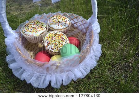 Easter cakes and colored eggs with a wicker basket lined with tulle and ribbons