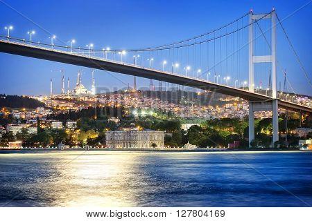 Bosphorus Bridge at night with moon path. Istanbul Turkey.