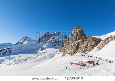 Jungfraujoch Switzerland - December 28 2015 - Tourists on the winter hiking pass outside the Jungfraujoch railway station with view of Jungfrau andtThe Sphinx Observatory.